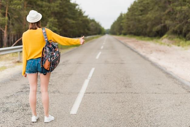 Long coup de femme faisant de l'auto-stop Photo gratuit