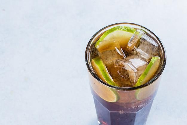 Long island avec glace et citron vert sur la table de fond clair. cocktail de thé glacé Photo Premium