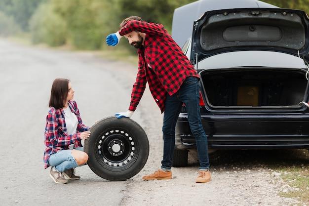 Long plan du couple qui change de pneu Photo gratuit