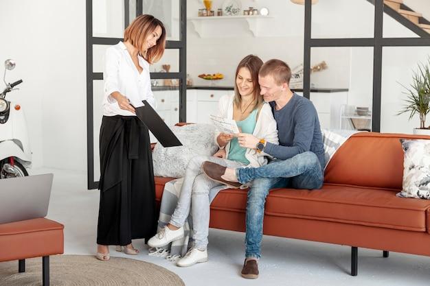 Long shot agent immobilier parlant avec un homme et une femme Photo gratuit