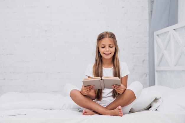 Long shot blonde petite fille lisant un livre Photo gratuit