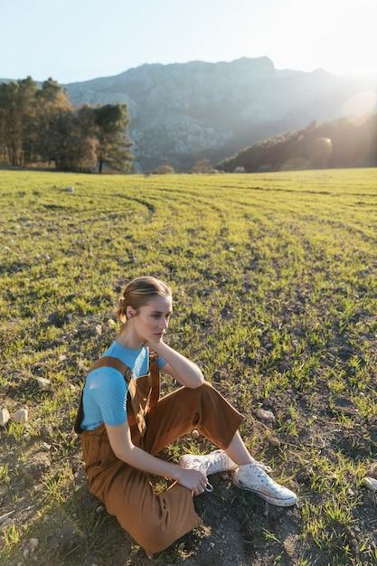 Long shot femme assise sur l'herbe Photo gratuit