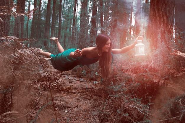 Long shot femme en lévitation dans la forêt avec lanterne Photo gratuit