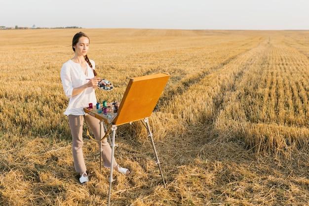 Long shot femme peignant dans la nature Photo gratuit