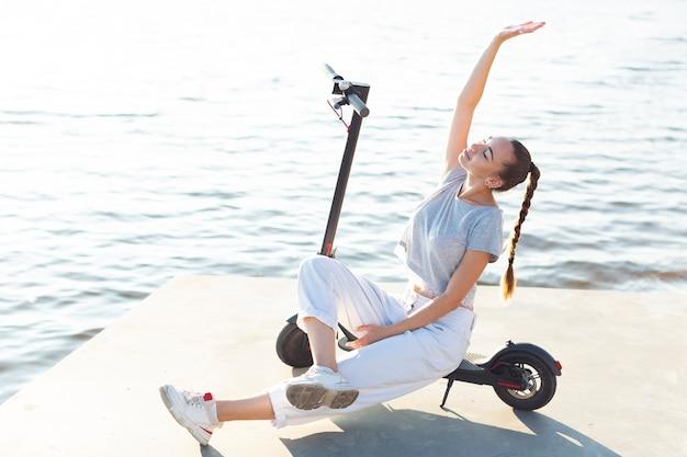 Long shot femme posant sur un scooter Photo gratuit