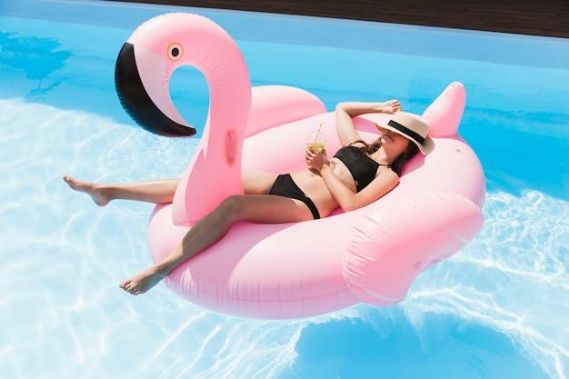 Long shot fille couchée sur flamingo floatie Photo gratuit