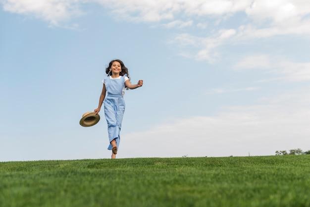 Long shot fille marchant pieds nus sur l'herbe Photo gratuit