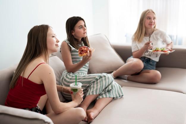 Long shot filles en train de manger une pizza sur un canapé Photo gratuit