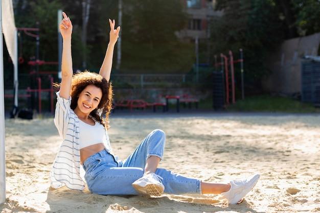 Long Shot Smiley Woman Posant à Côté D'un Terrain De Volley-ball Photo gratuit