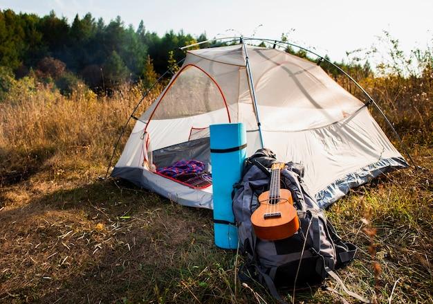Long shot de la tente blanche avec bagages et guitare Photo gratuit
