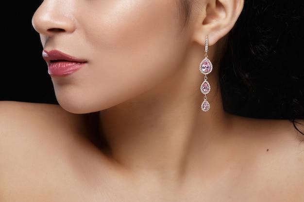 Longue boucle d'oreille avec des pierres précieuses violettes pendent de l'oreille de la femme Photo gratuit
