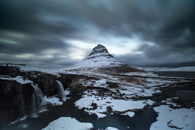 Longue exposition de la montagne kirkjufell sous un nuage en mouvement Photo Premium