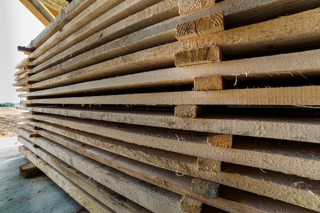 Longue Pile De Planches De Bois Soigneusement Empilées à L'intérieur De La Pièce Du Grenier En Construction. Photo Premium