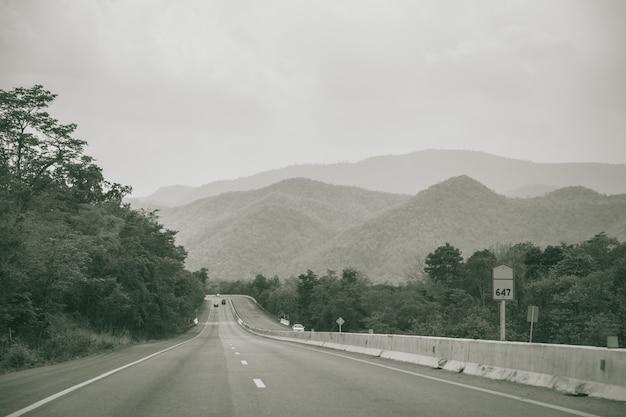 Longue route droite avec vue sur la montagne de la campagne brume photographie autoroute en noir et blanc Photo Premium