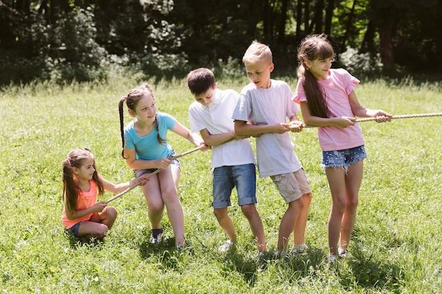 Longue tir d'enfants jouant au tir à la corde Photo gratuit