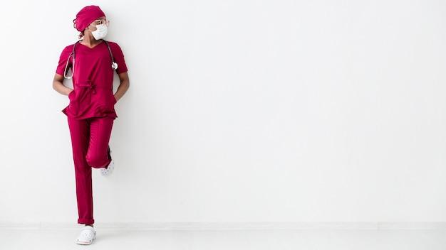 Longue Vue De La Femme Médecin S'appuyant Sur Le Mur Blanc Photo gratuit
