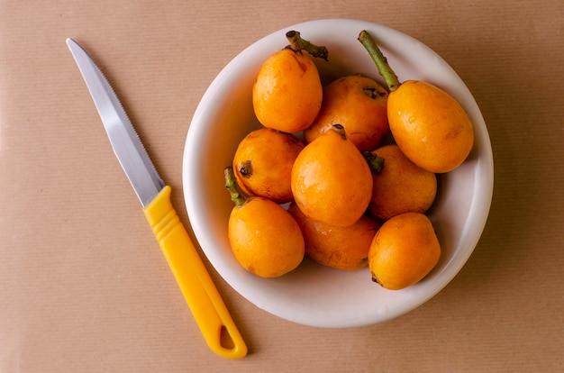 Loquats frais sur une assiette blanche et un couteau sur beige Photo Premium
