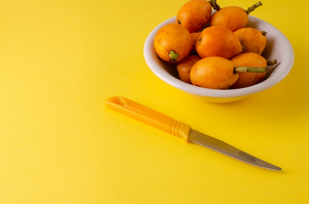 Loquats frais mûrs sur plaque blanche et nkife sur jaune Photo Premium