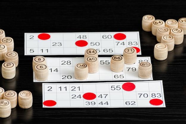 Loto en bois, fûts et cartes pour jouer sur une table noire Photo Premium