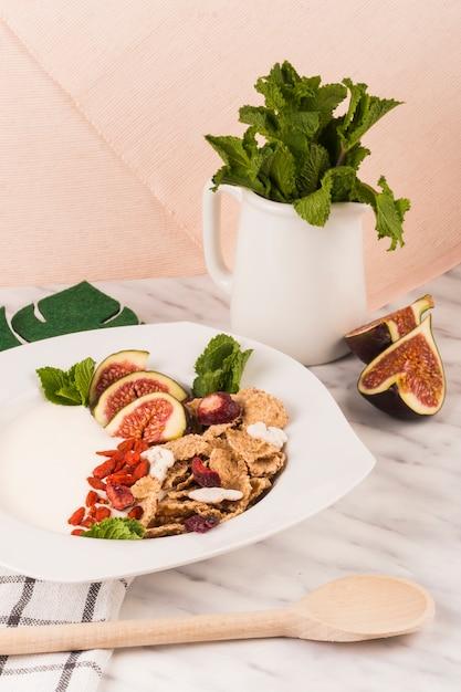 Louche en bois près du petit-déjeuner sain à la menthe laisse dans la cruche sur le comptoir de marbre Photo gratuit