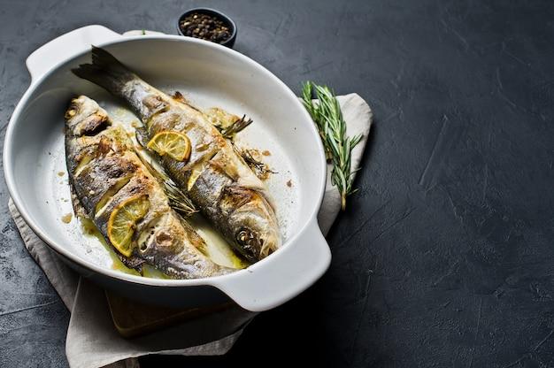 Loup de mer cuit au four dans un plat allant au four. Photo Premium