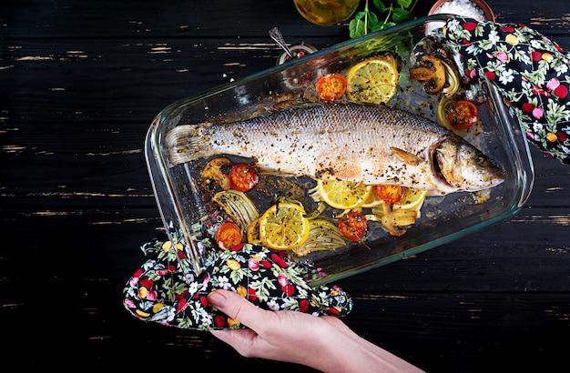 Loup de mer cuit dans un plat allant au four avec des épices et des légumes à tenir dans les mains. Photo Premium