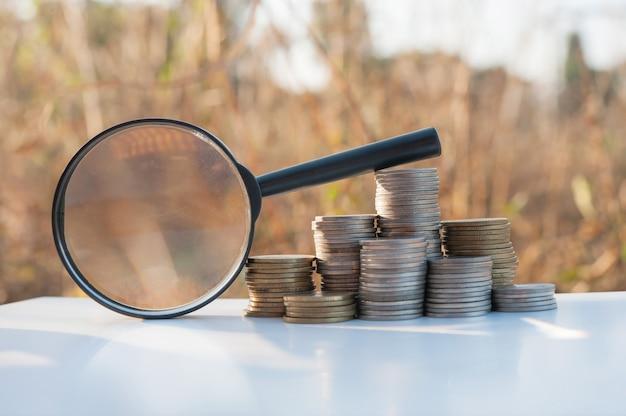 Loupe d'économiser de l'argent avec pile de pièces de plus en plus sur la nature coucher de soleil Photo Premium