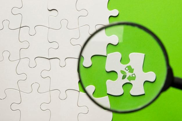 Loupe masse sur puzzle blanc avec l'icône de recyclage sur la surface verte Photo gratuit