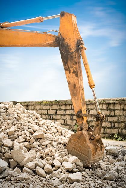 Lourde excavatrice d'organge avec pelle debout sur la colline avec des rochers Photo Premium