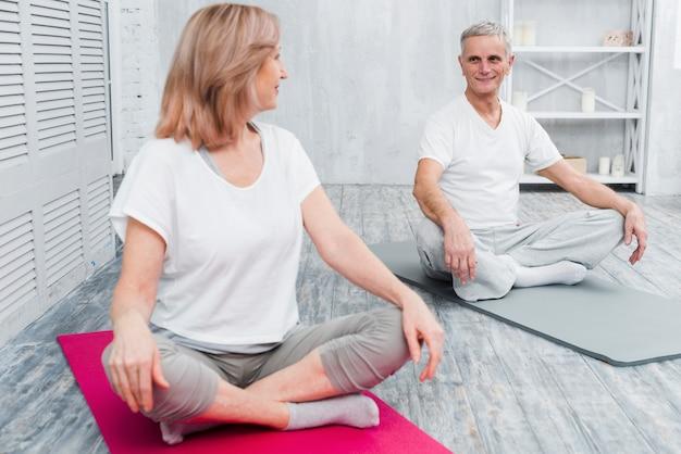 Loving couple heureux se regardant avant de commencer le yoga Photo gratuit