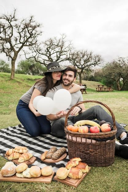 Loving jeune couple assis avec des aliments cuits au four et des fruits sur le panier de pique-nique dans le parc Photo gratuit