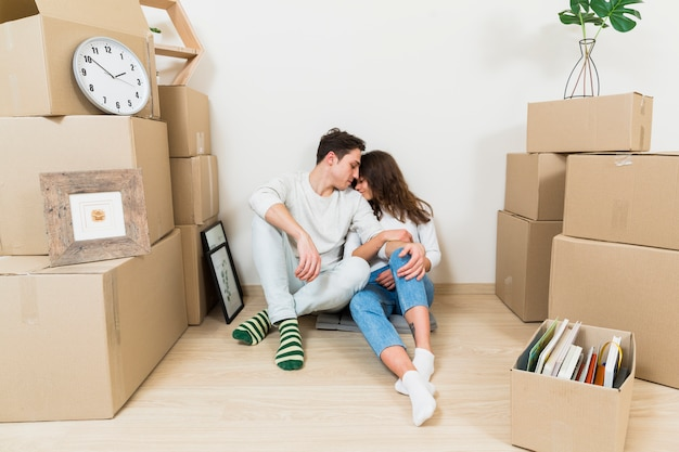 Loving jeune couple assis entre la pile de boîtes en carton dans leur nouvel appartement Photo gratuit