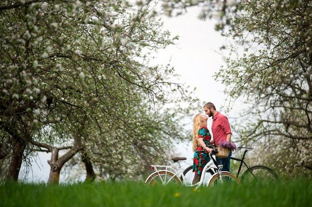 Loving jeune couple avec des vélos dans le jardin de printemps Photo Premium