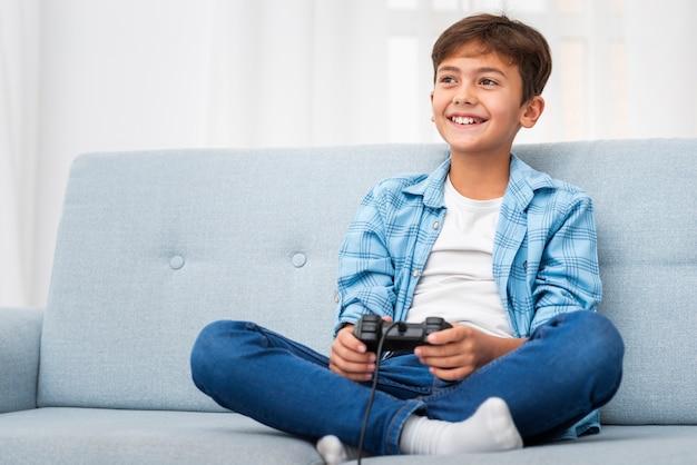 Low angle boy jouant avec joystick Photo gratuit