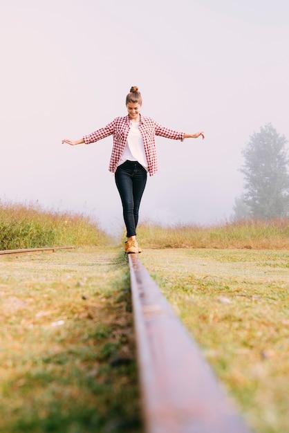 Low angle jeune fille en équilibre sur le chemin de fer Photo gratuit