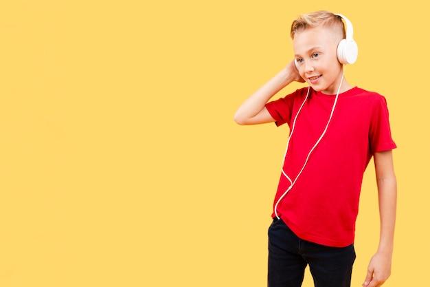Low angle jeune garçon écoute de la musique Photo gratuit