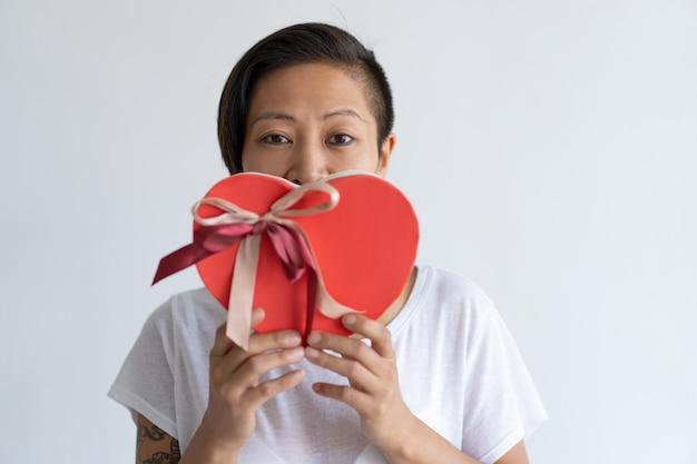 Ludique femme tenant une boîte cadeau en forme de coeur devant la bouche Photo gratuit