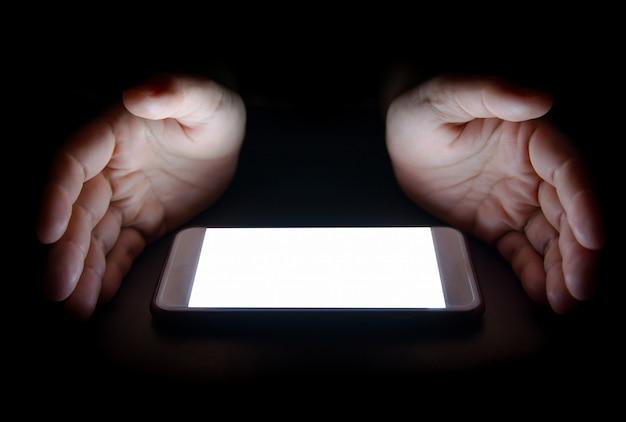 La Lumière Blanche Du Smartphone Reflète Votre Main La Nuit Dans L'obscurité Photo Premium