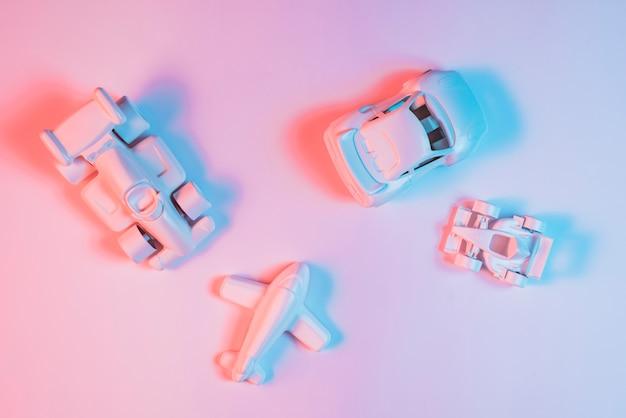 Lumière De Couleur Bleue Sur Les Jouets Du Véhicule De Transport Sur Fond Rose Photo gratuit