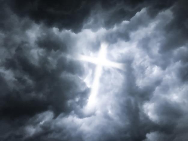 La lumière du crucifix traverse des nuages sombres avec saint et ciel. Photo Premium