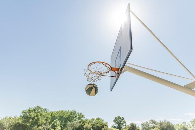 Lumière du soleil sur le cerceau de basket-ball contre le ciel bleu clair Photo gratuit