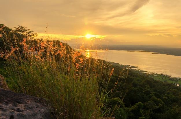 La lumière du soleil reflète la surface de l'eau et l'herbe est sur les montagnes Photo Premium