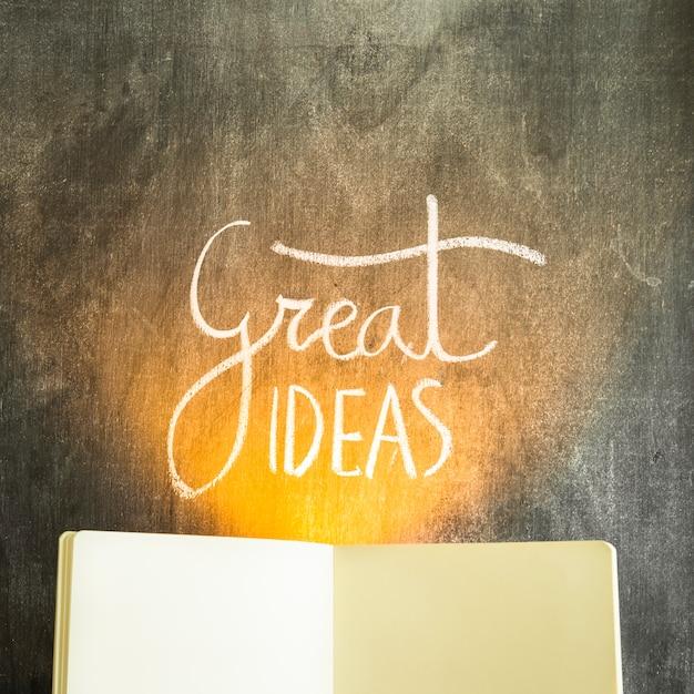 Lumière sur le texte de grandes idées sur tableau noir avec un livre ouvert vide Photo gratuit