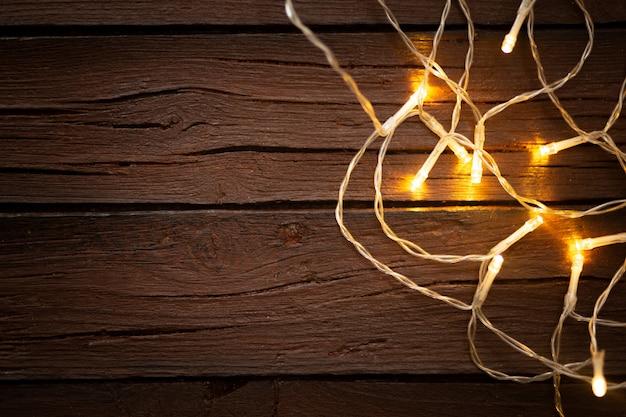 Lumières de noël sur un vieux fond en bois texturé Photo gratuit