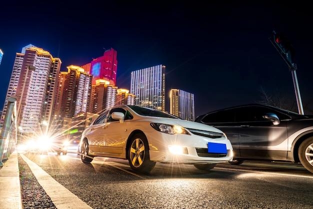 Lumières de voiture floues et vues nocturnes de paysages architecturaux urbains Photo Premium