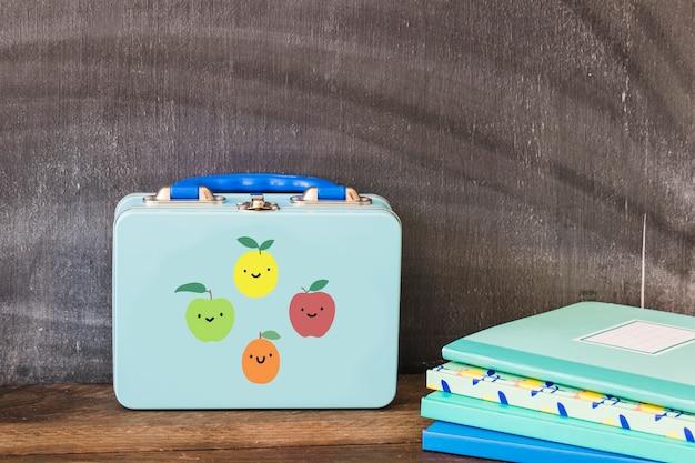 Lunchbox près de la pile de cahiers Photo gratuit