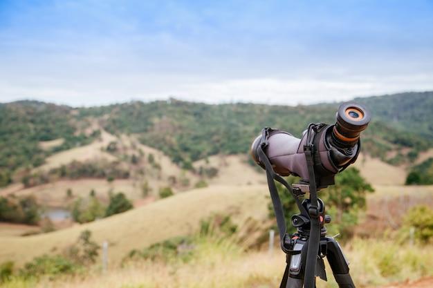 Lunette d'observation ou monoculaire sur montagne verte floue Photo Premium