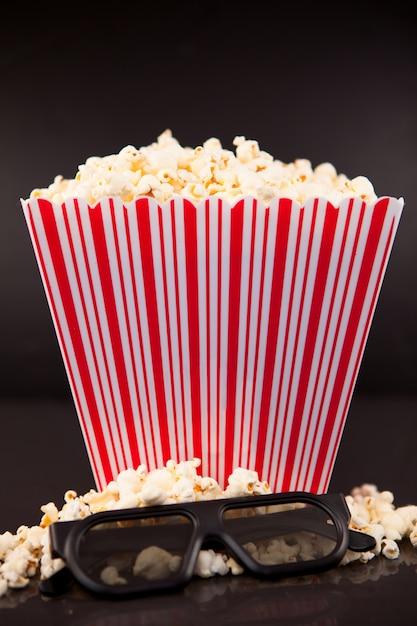 Lunettes 3d sur pop-corn aux pieds d'une boîte de maïs soufflé Photo Premium
