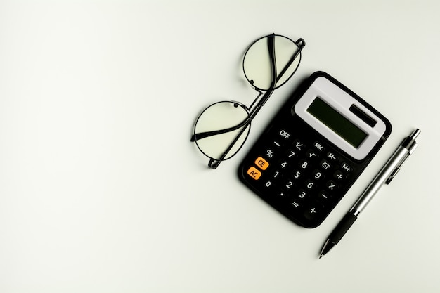 Lunettes, calculatrice et et un stylo sur la table blanche. - vue de dessus avec espace de copie. Photo Premium