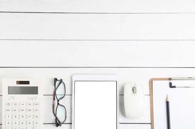 Lunettes, calculatrice et tablette sur bureau blanc et soigné Photo gratuit